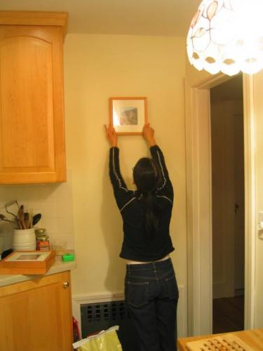 Serena hanging picture in kitchen